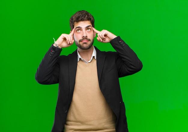 Junger geschäftsmann, der verwirrt oder zweifelnd sich fühlt, auf eine idee sich konzentriert, stark denkt und schaut, um raum auf seite gegen grüne wand zu kopieren