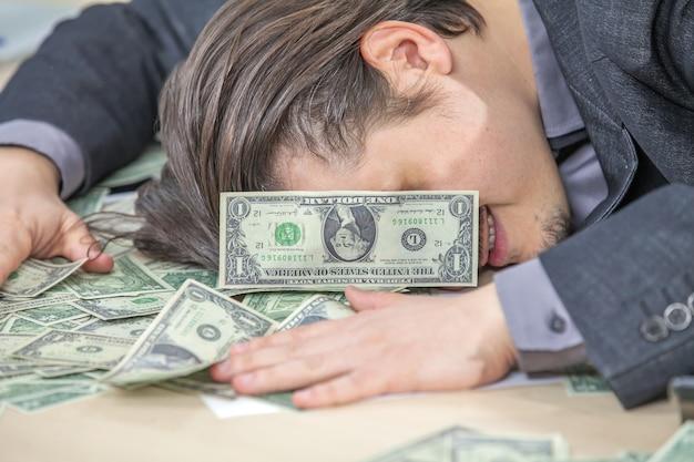 Junger geschäftsmann, der von seinem büro arbeitet und bargeld zählt