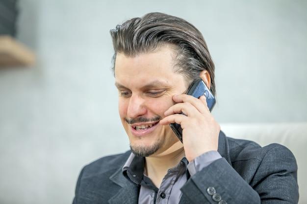 Junger geschäftsmann, der von seinem büro arbeitet, während er am telefon spricht