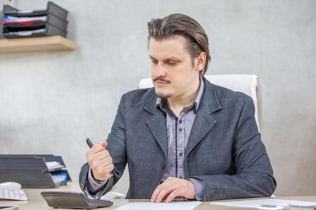 Junger geschäftsmann, der von seinem büro aus arbeitet - das konzept der harten arbeit