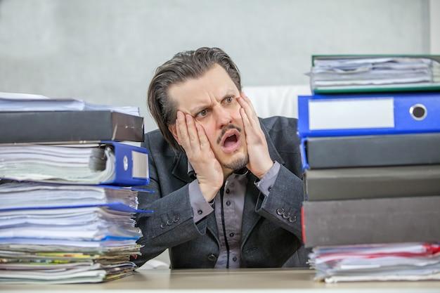 Junger geschäftsmann, der von seinem büro aus arbeitet - das konzept des stresses