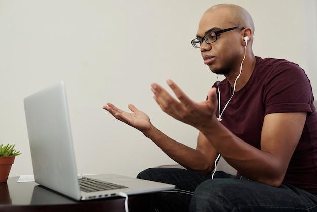 Junger geschäftsmann, der von zu hause aus arbeitet und seinen kollegen per video anruft, um das projekt zu besprechen