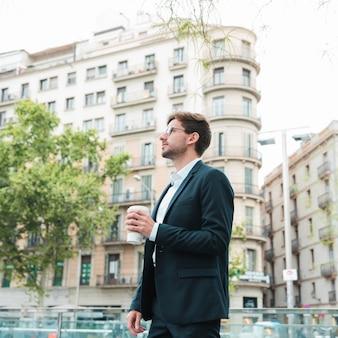 Junger geschäftsmann, der vor dem gebäude hält kaffeetasse in der hand steht