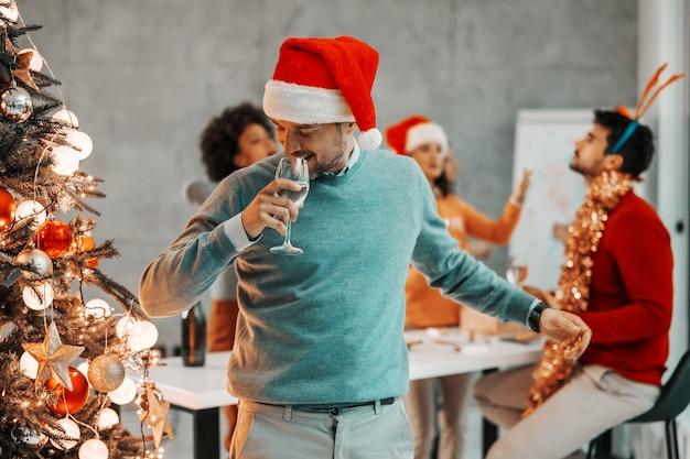 Junger geschäftsmann, der weihnachten in gesellschaft feiert.
