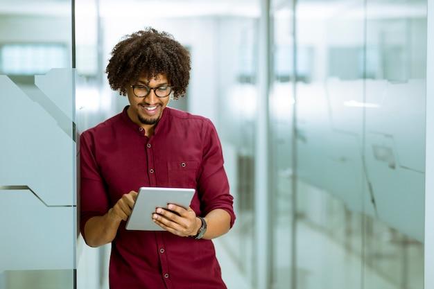 Junger geschäftsmann des afroamerikaners mit der tablette, die im büro steht