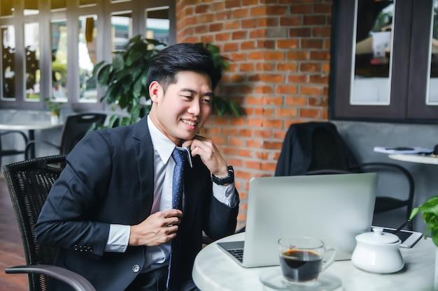 Junger geschäftsmann erfolgreich, die finanzinformationen im laptop beim sitzen an der kaffeestube schauend.