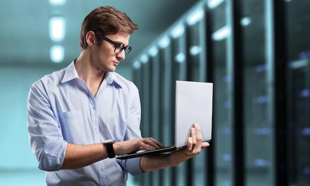Junger geschäftsmann es ingenieur mit aluminium-laptop im serverraum