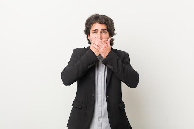 Junger geschäftsmann gegen eine weiße wand entsetzte bedeckungsmund mit den händen.