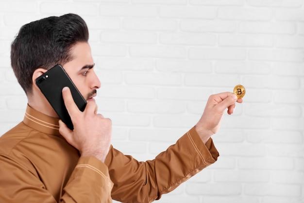 Junger geschäftsmann hält ein glänzendes goldenes bitcoin in seinen händen