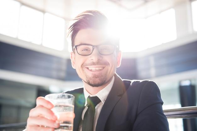 Junger geschäftsmann hält ein glas wasser.