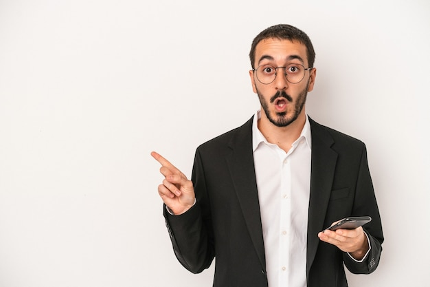 Junger geschäftsmann hält ein mobiltelefon isoliert auf weißem hintergrund und zeigt zur seite