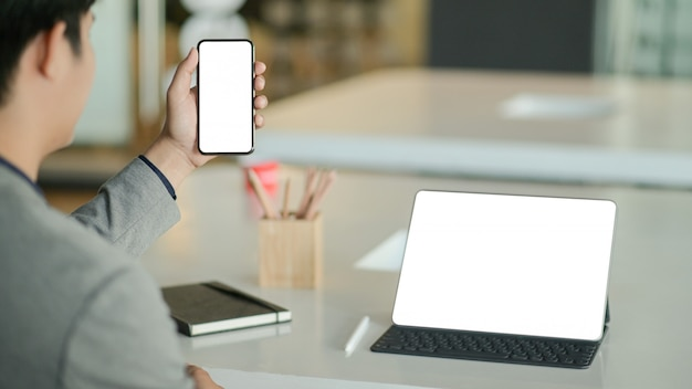 Junger geschäftsmann hält ein smartphone mit leerem bildschirm in der hand und einen laptop mit leerem bildschirm auf dem schreibtisch.