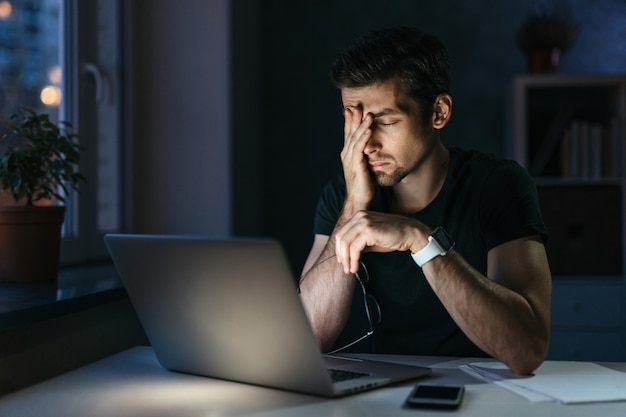 Junger geschäftsmann hat kopfschmerzen, während er spät in der nacht überstunden mit laptop im büro zu hause macht.