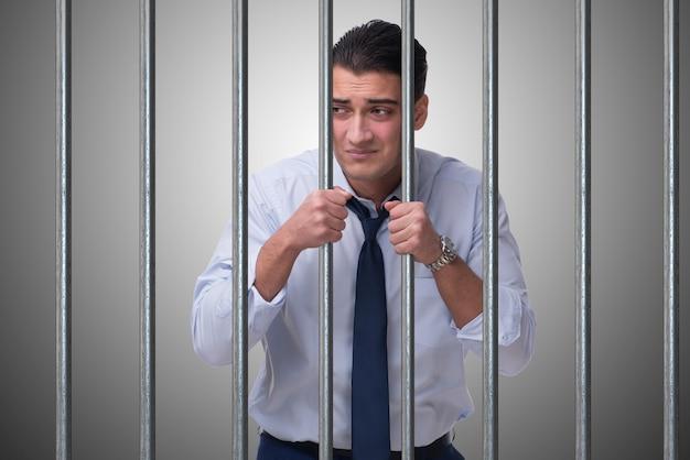 Junger geschäftsmann hinter den gittern im gefängnis
