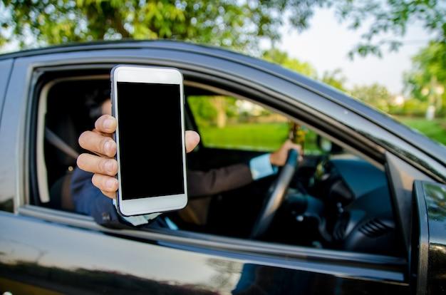 Junger geschäftsmann hob sein smartphone im auto an.