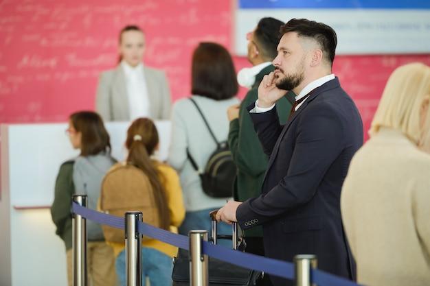 Junger geschäftsmann im anzug, der mit dem handy spricht, während er in einer warteschlange steht und auf seine registrierung wartet
