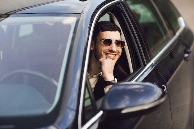Junger geschäftsmann im anzug und in den schwarzen gläsern, die sein auto fahren. bussines aussehen. probefahrt des neuen autos