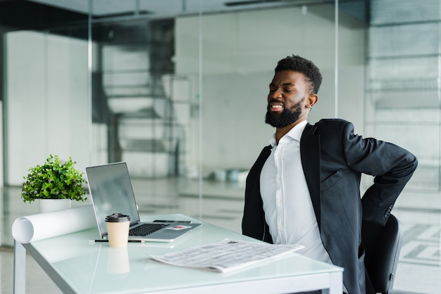 Junger geschäftsmann im büro am schreibtisch, der unter rückenschmerzen im büro leidet