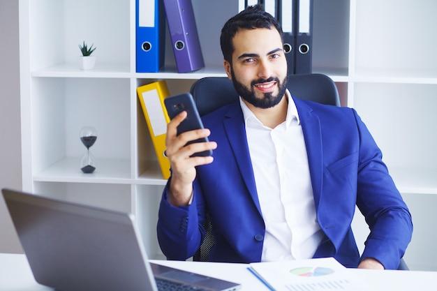 Junger geschäftsmann im büro, das an computer arbeitet