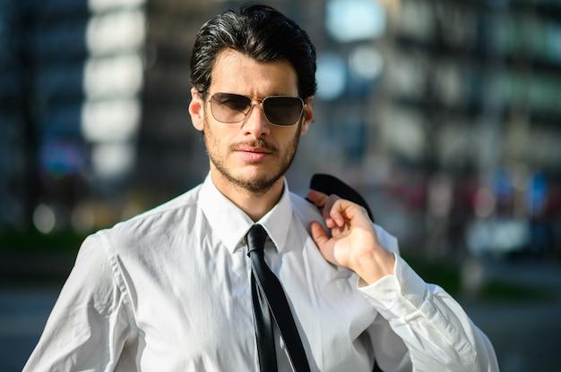 Junger geschäftsmann im freien, der sonnenbrille trägt und seine jacke an einem sonnigen tag hält