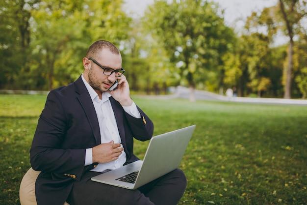 Junger geschäftsmann im weißen hemd, im klassischen anzug, in der brille. mann sitzt auf weichem hocker, arbeitet am laptop-pc, spricht mit dem handy im stadtpark auf grünem rasen im freien. mobiles büro, geschäftskonzept.