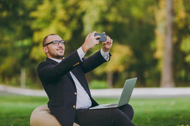 Junger geschäftsmann im weißen hemd, im klassischen anzug, in der brille. mann sitzt auf weichem hocker mit laptop-pc und macht selfie auf dem handy im stadtpark auf grünem rasen im freien. geschäftskonzept für mobiles büro.