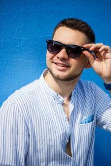 Junger geschäftsmann in blauem hemd und schwarzer brille auf blauem hintergrund