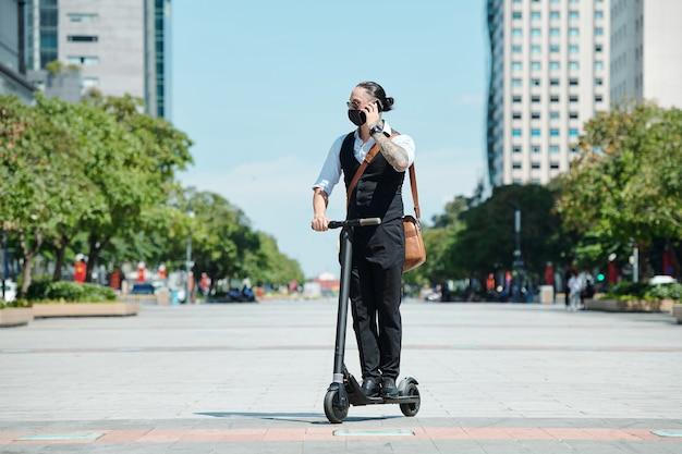 Junger geschäftsmann in der medizinischen maske, die auf roller reitet und am telefon mit spricht