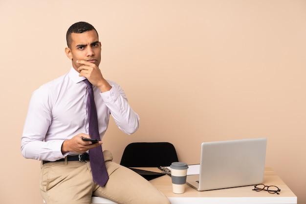 Junger geschäftsmann in einem büro, das eine idee denkt