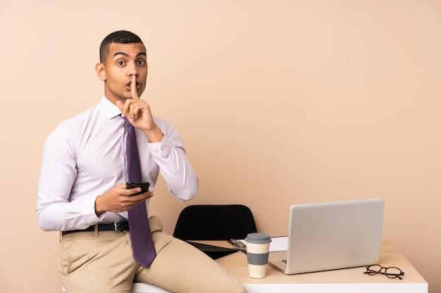 Junger geschäftsmann in einem büro, das schweigengeste tut