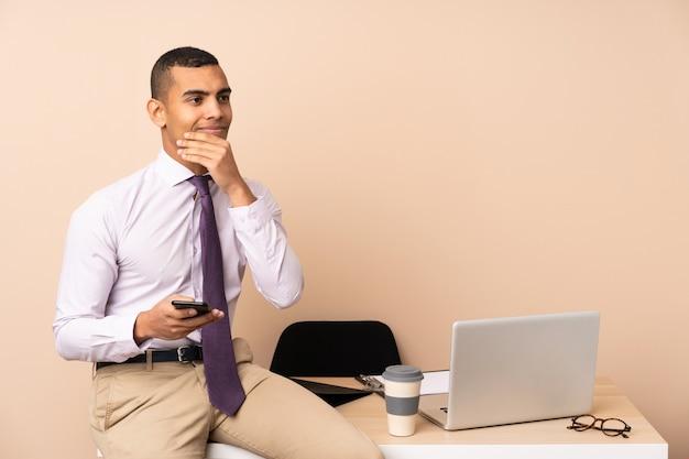 Junger geschäftsmann in einem büro eine idee denkend