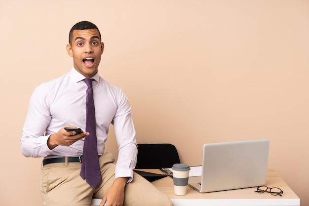 Junger geschäftsmann in einem büro mit überraschendem gesichtsausdruck