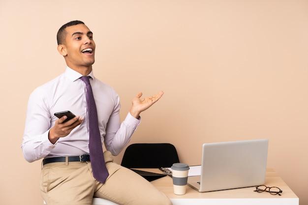 Junger geschäftsmann in einem büro mit überraschungsgesichtsausdruck