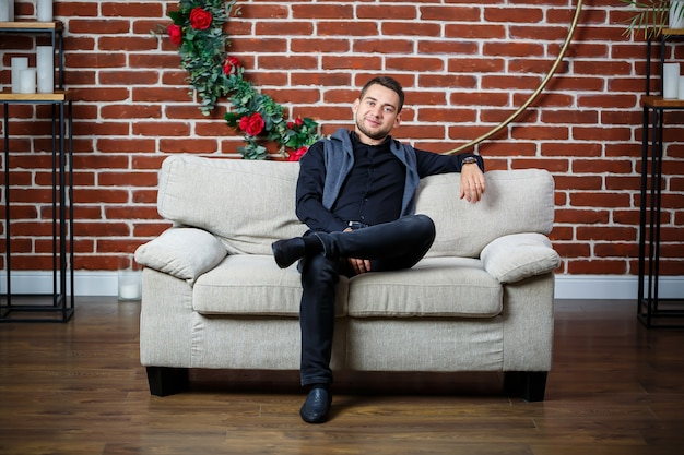 Junger geschäftsmann in einem hemd auf einem sofa