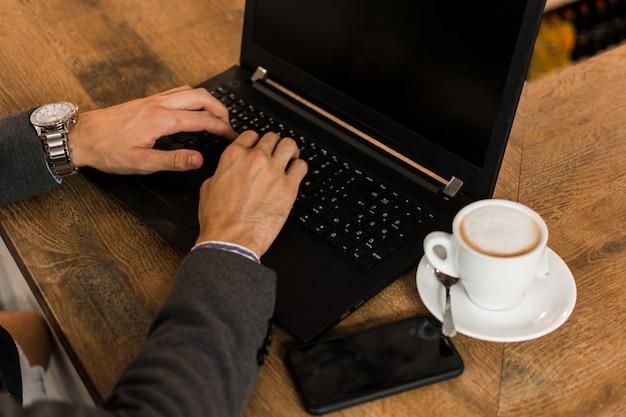 Junger geschäftsmann in einer kneipe, die mit seinem laptop arbeitet. nahansicht