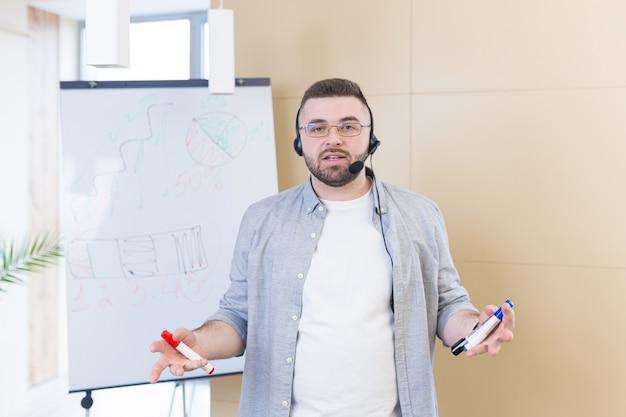 Junger geschäftsmann in freizeitkleidung, die eine headset-online-besprechungspräsentation trägt