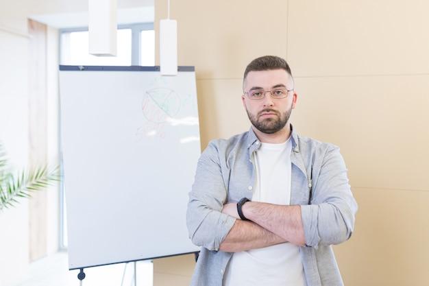Junger geschäftsmann in freizeitkleidung online-meeting-präsentation oder training unter verwendung einer laptop-webcam und eines flipcharts mit markern