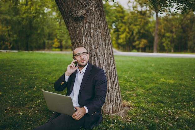 Junger geschäftsmann in hemd, anzug, brille. mann sitzt auf grasboden, spricht mit dem handy, arbeitet am laptop-pc im stadtpark auf grünem rasen im freien in der natur. mobiles büro, geschäftskonzept.