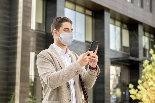 Junger geschäftsmann in schutzmaske, der das handy vor seinem gesicht hält und online spricht, während er auf der straße steht
