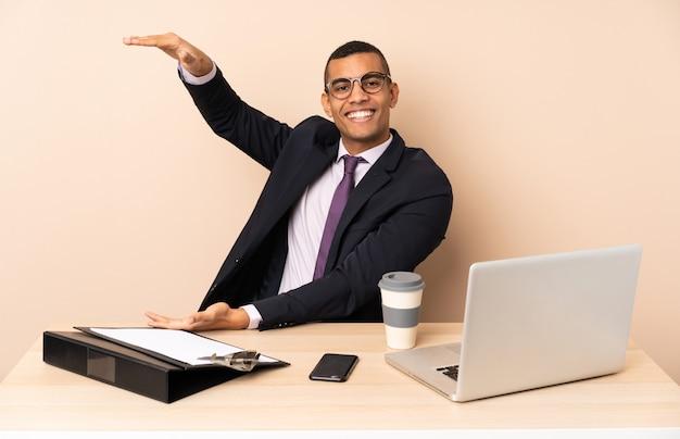 Junger geschäftsmann in seinem büro mit einem laptop und anderen dokumenten, die copyspace halten, um eine anzeige einzufügen