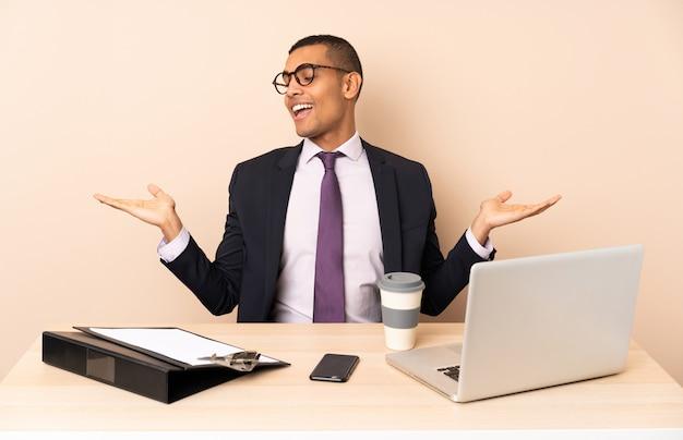 Junger geschäftsmann in seinem büro mit einem laptop und anderen dokumenten, die copyspace mit zwei händen halten