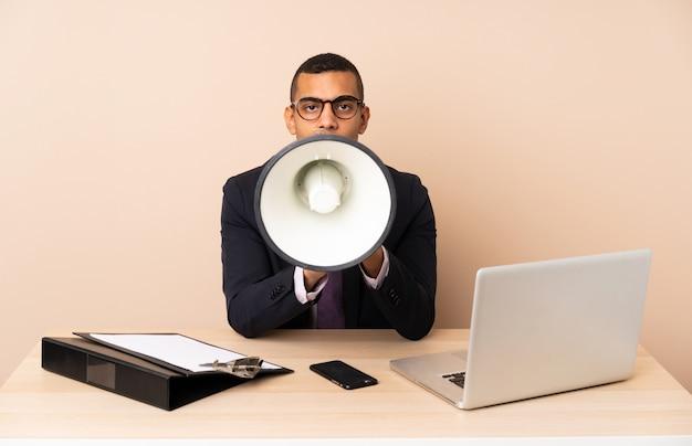 Junger geschäftsmann in seinem büro mit einem laptop und anderen dokumenten, die durch ein megaphon schreien