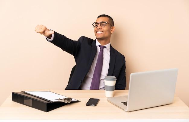 Junger geschäftsmann in seinem büro mit einem laptop und anderen dokumenten, die eine daumen hoch geste geben