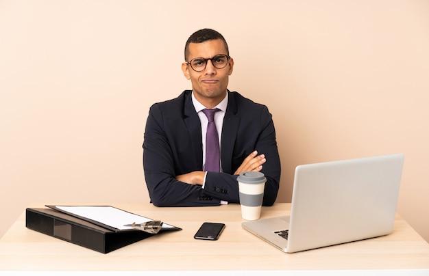 Junger geschäftsmann in seinem büro mit einem laptop und anderen dokumenten, die gestört sich fühlen