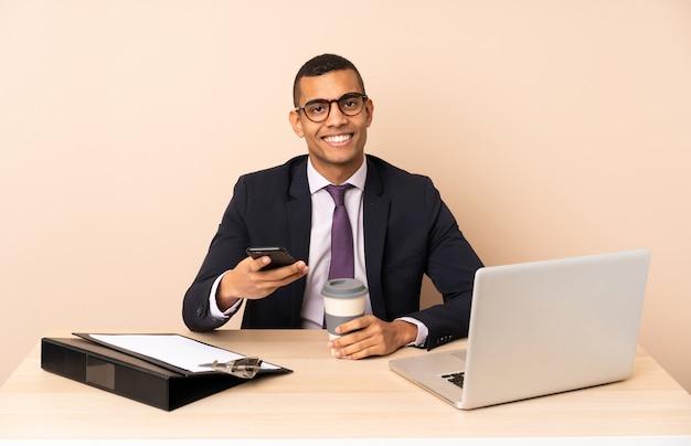 Junger geschäftsmann in seinem büro mit einem laptop und anderen dokumenten, die kaffee halten, um und ein mobile wegzunehmen