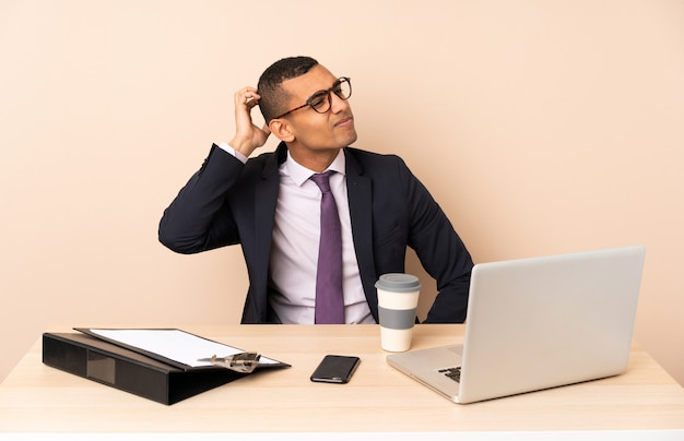 Junger geschäftsmann in seinem büro mit einem laptop und anderen dokumenten, die zweifel beim kratzen des kopfes haben