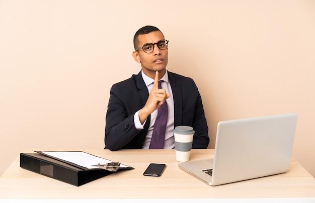 Junger geschäftsmann in seinem büro mit einem laptop und anderen dokumenten frustriert und zeigt nach vorne