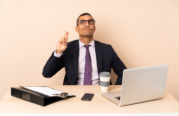 Junger geschäftsmann in seinem büro mit einem laptop und anderen dokumenten mit daumen drücken und das beste wünschen