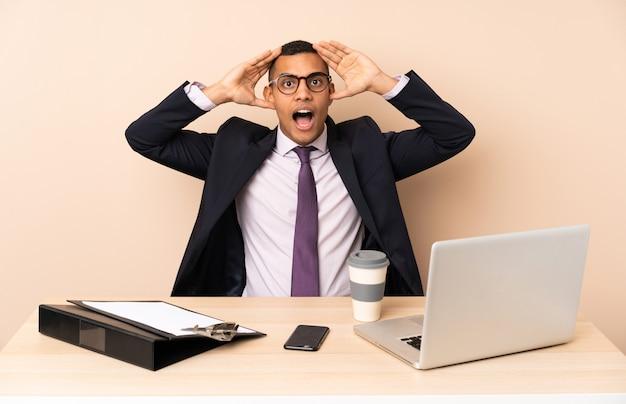 Junger geschäftsmann in seinem büro mit einem laptop und anderen dokumenten mit überraschendem ausdruck