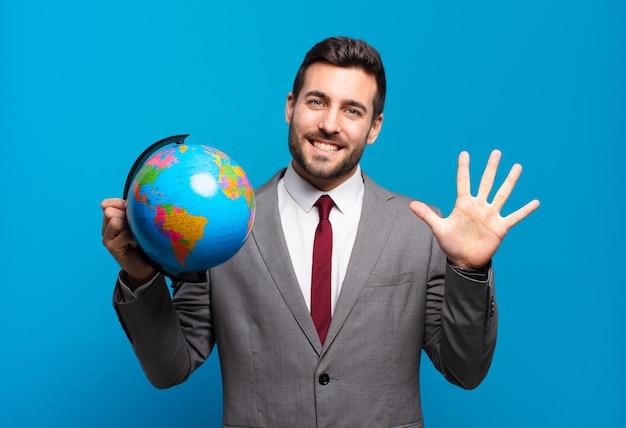 Junger geschäftsmann lächelt und sieht freundlich aus, zeigt nummer fünf oder fünf mit der hand nach vorne, zählt herunter und hält eine weltkugelkarte